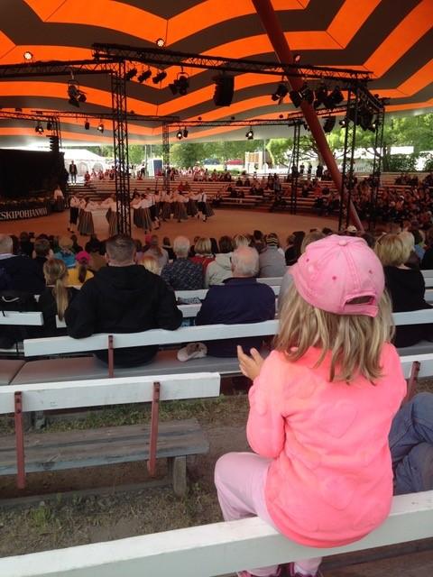 Pikkutyttö taputtaa areenan katsomossa.