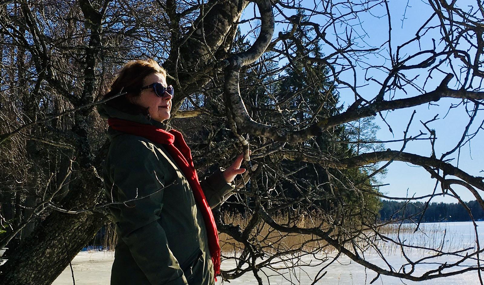 Maria Kalaniemi katsoo järvelle kirkkaassa helmikuisessa auringonpaisteessa.