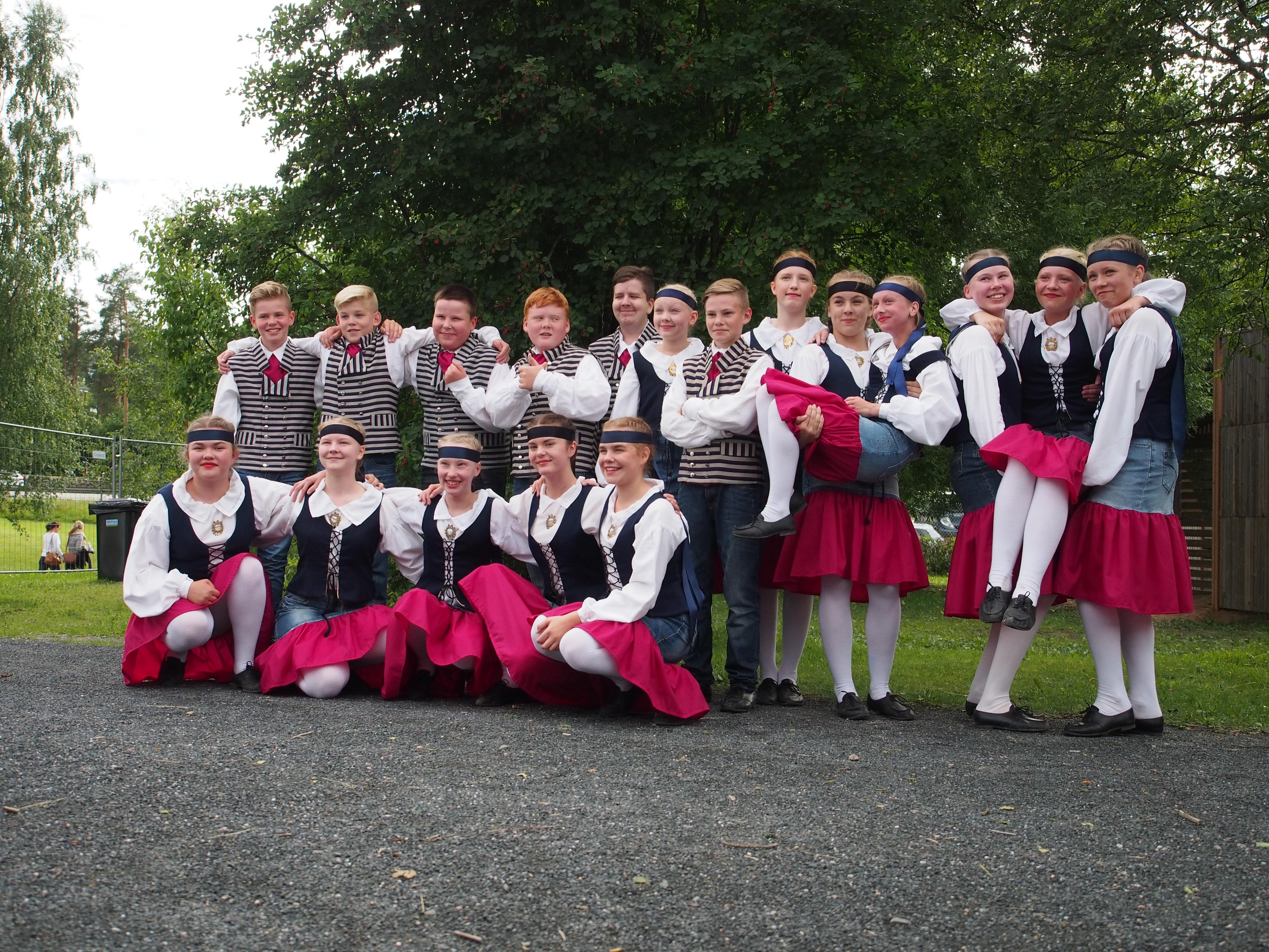 Kaustislainen kansantanssiryhmä JunioriOttoset poseeraa keikan jälkeisissä iloisissa tunnelmissa vuonna 2016. Kuvan on ottanut Eveliina Aho.
