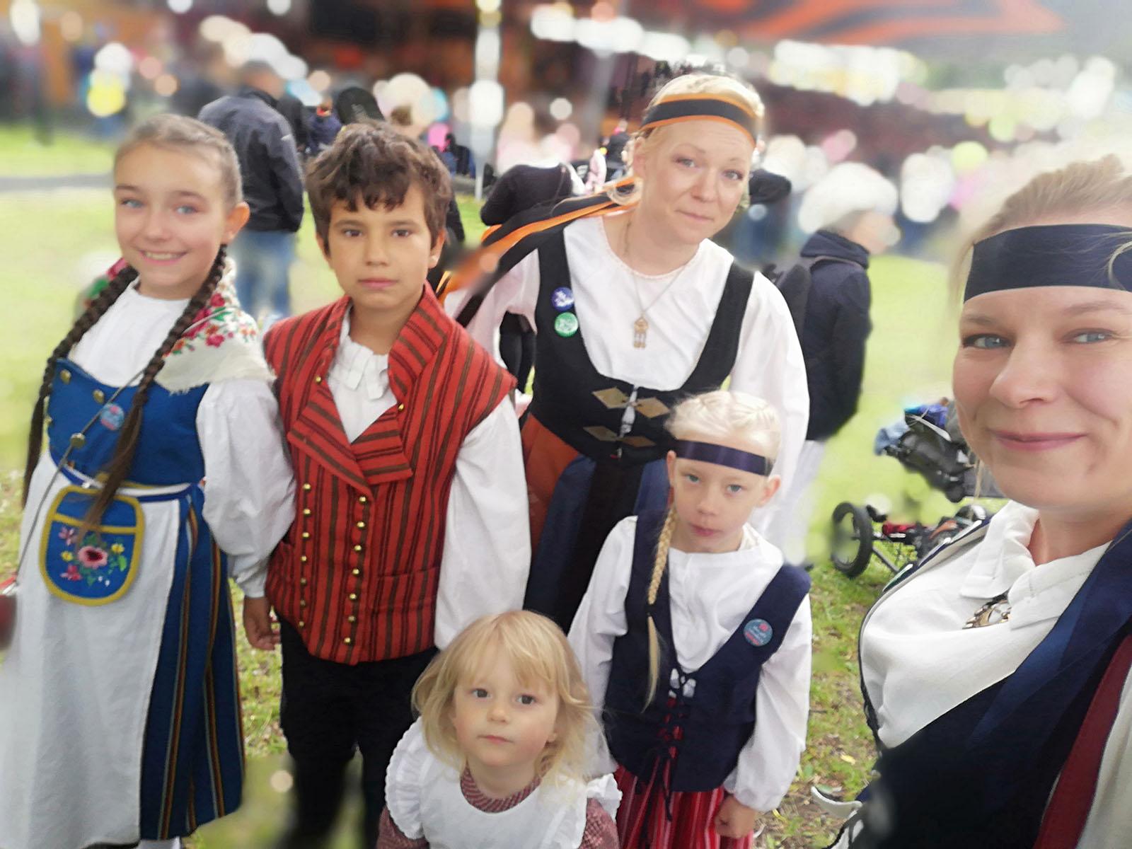 Veera Valo ja Hanna-siskonsa ryhmäkuvassa festivaaleilla 2019. Kaikilla on kansallispuvut päällä.