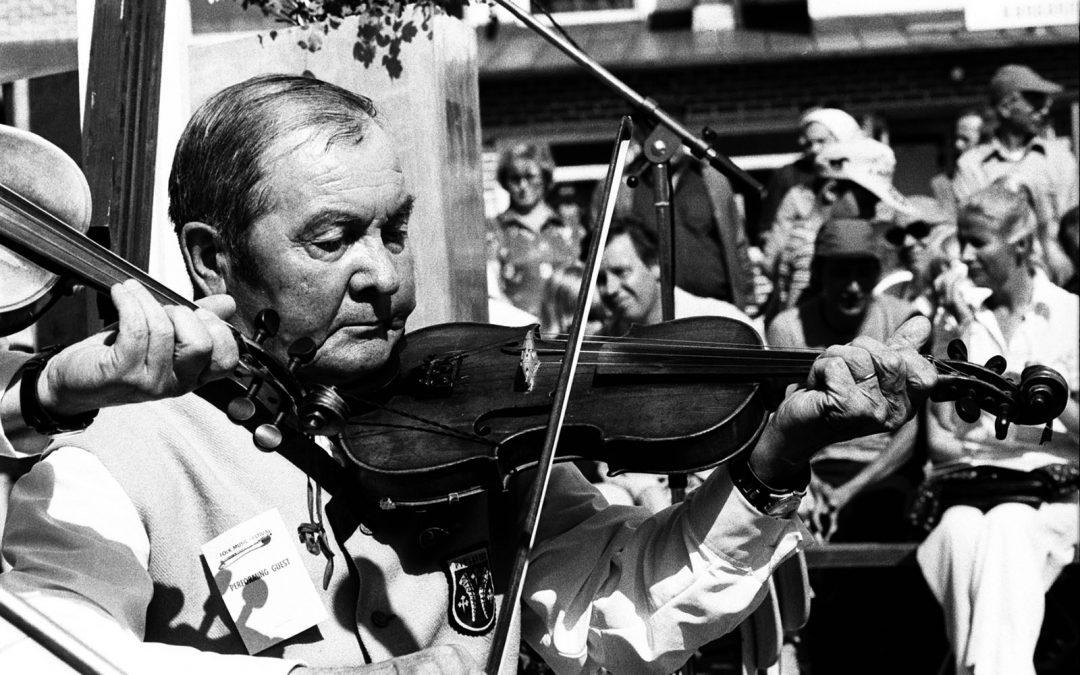 Tuure Niskanen soittaa viulua keskittyneenä yleisön keskellä.